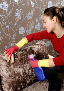 woman cleaning spots on a microfiber couch